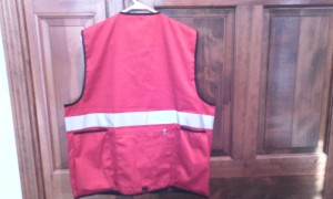 Back of Red Vest (without logo) as example. The back of the vest features a thick safety reflective strip, two deep pockets to carry water bottles, and a large zippered pocket.